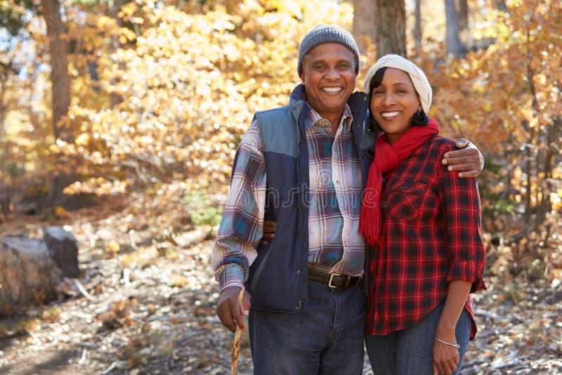 Pares afroamericanos mayores que caminan a través de arbolado de la caída foto de archivo libre de regalías