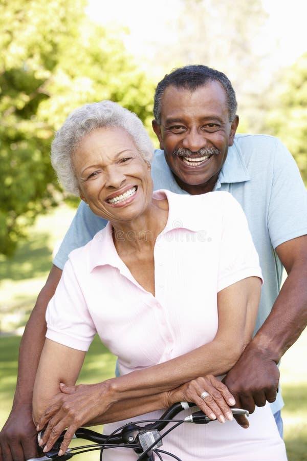 Pares afroamericanos mayores que completan un ciclo en parque fotos de archivo libres de regalías