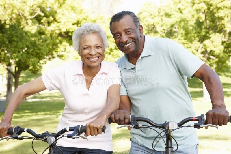 Pares afroamericanos mayores que completan un ciclo en parque foto de archivo
