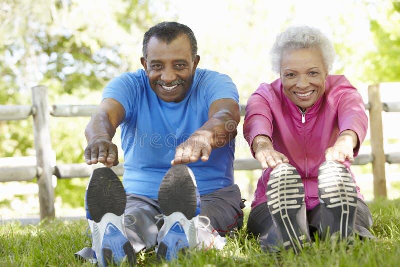 Pares afroamericanos mayores que ejercitan en parque imagen de archivo libre de regalías