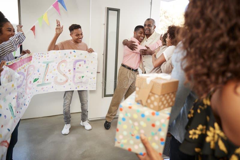 Pares afroamericanos mayores que llegan a casa a un partido de sorpresa de la familia, foco selectivo imagenes de archivo