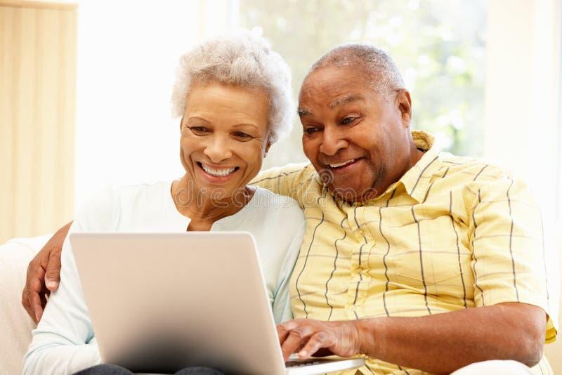 Pares afroamericanos mayores usando el ordenador portátil imagen de archivo