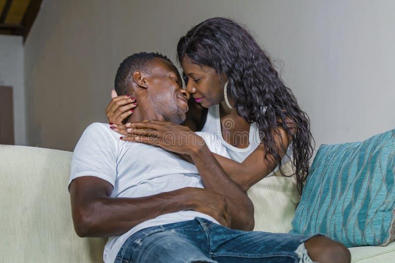 Pares afroamericanos negros felices que abrazan en casa la sonrisa del sofá del sofá de la sala de estar alegre divirtiéndose rel imágenes de archivo libres de regalías