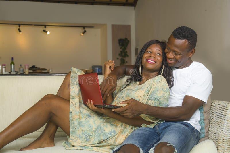 Pares afroamericanos negros felices y hermosos jovenes en el amor que goza en el sofá del sofá de la sala de estar con el ordenad foto de archivo libre de regalías