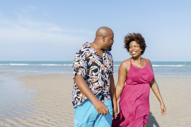 Pares afroamericanos que caminan en la playa foto de archivo