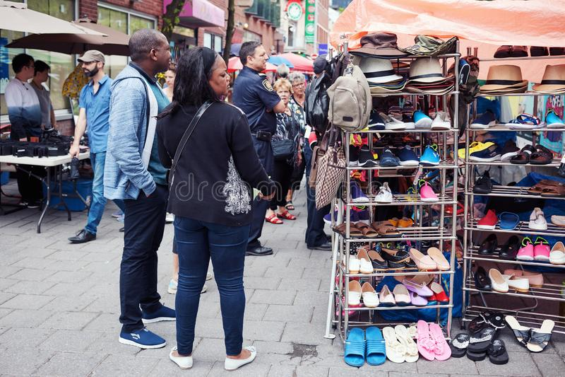 Pares afroamericanos que hacen compras que miran los productos en el contador de un mercado al aire libre Chinatown en Montreal,  foto de archivo