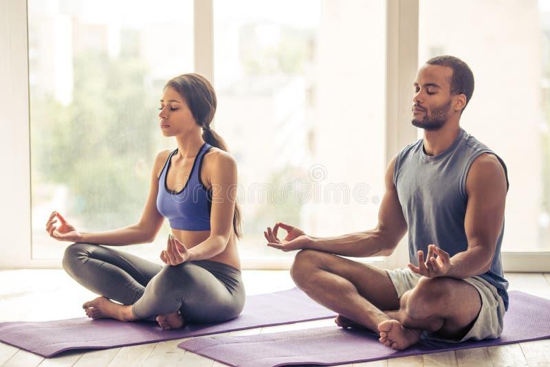 Pares afroamericanos que hacen yoga fotos de archivo