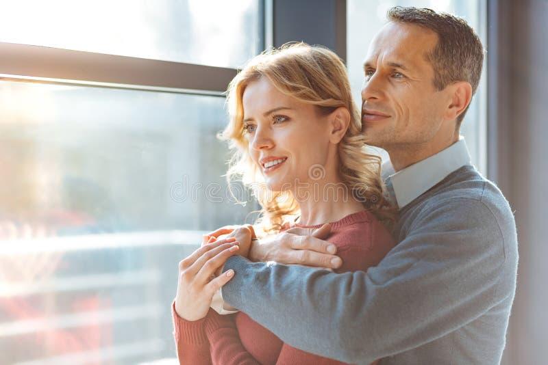 Pares agradáveis alegres que olham na janela fotografia de stock royalty free