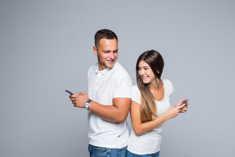 Pares agradáveis com telefones homem que olha no telefone da mulher isolado no cinza foto de stock