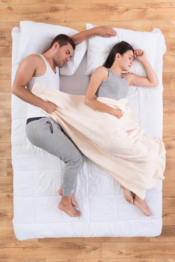Pares agradáveis que dormem na cama imagem de stock