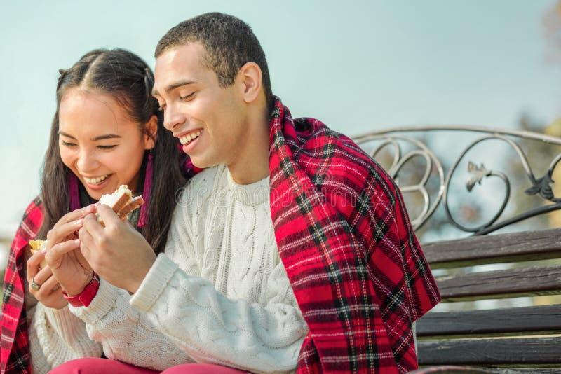 Pares agradables contentos que comen los bocadillos deliciosos en un aire fresco fotografía de archivo libre de regalías