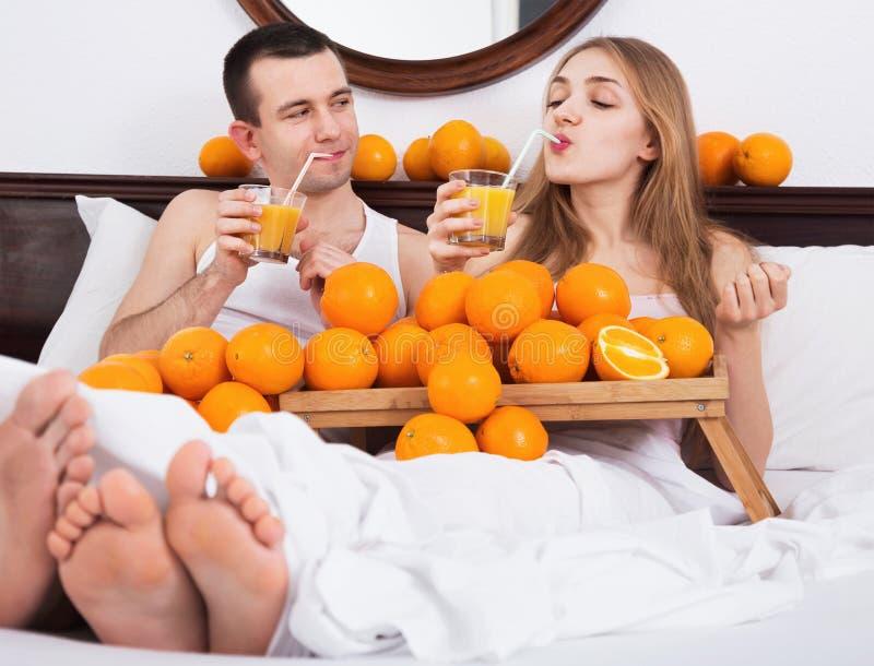Pares agradables jovenes con las naranjas y recientemente el jugo maduros imagen de archivo libre de regalías