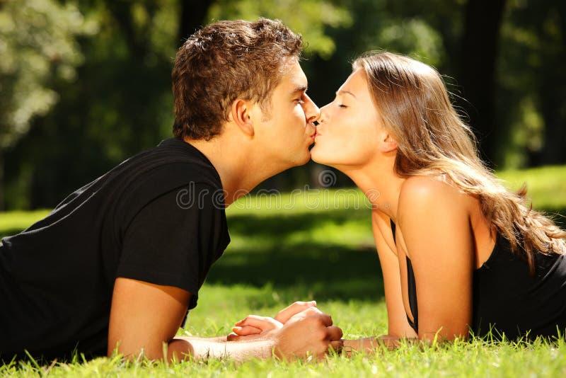 Pares agradables jovenes que se besan en el parque imagen de archivo
