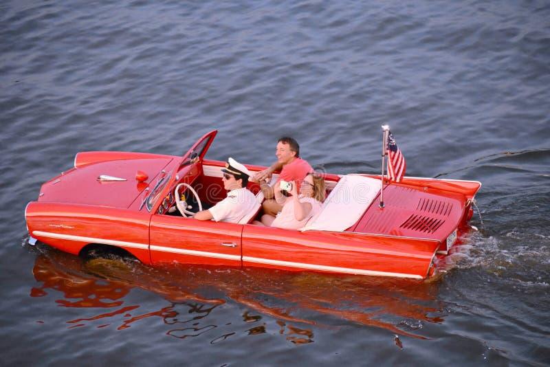 Pares agradables que disfrutan de paseo rojo anfibio del coche sobre el lago azul en el área de Buena Vista del lago fotos de archivo libres de regalías