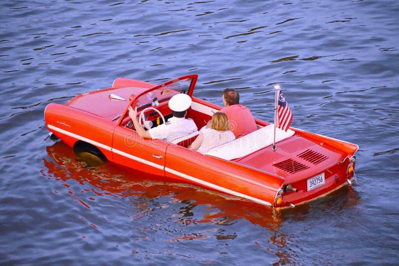 Pares agradables que disfrutan de paseo rojo anfibio del coche sobre el lago azul en el área de Buena Vista del lago imágenes de archivo libres de regalías