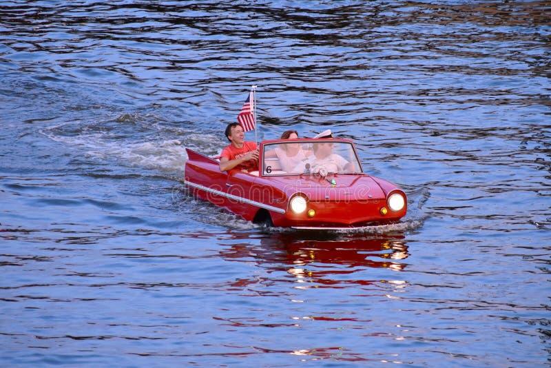Pares agradables que disfrutan de paseo rojo anfibio del coche sobre el lago azul en el área de Buena Vista del lago foto de archivo libre de regalías