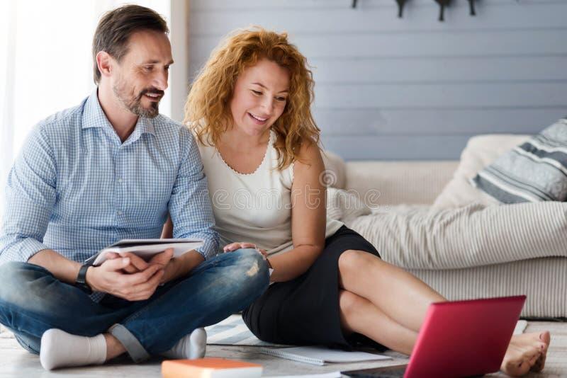 Pares agradables que se sientan en piso y que miran el ordenador portátil imagen de archivo libre de regalías