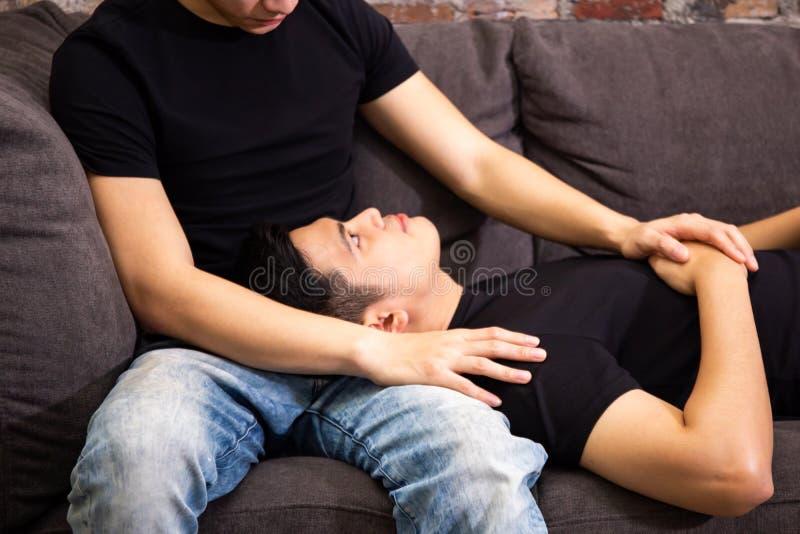 Pares alegres asiáticos que olham se junto no sofá na casa do vintage Retrato de homem gay felizes - conceito homossexual do amor imagem de stock