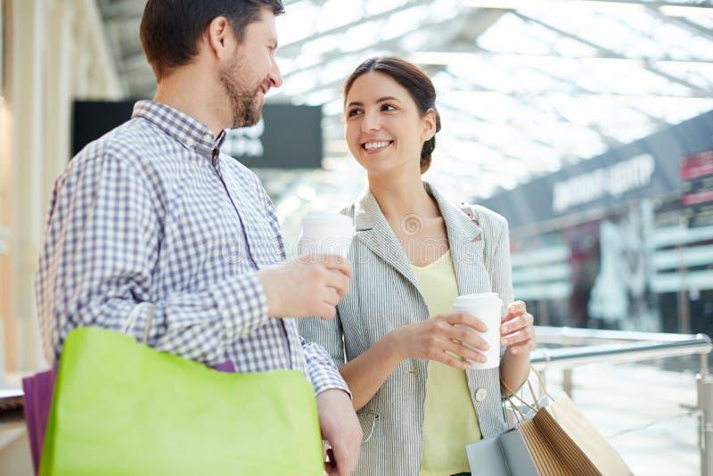 Pares alegres com café e sacos de compras imagem de stock royalty free