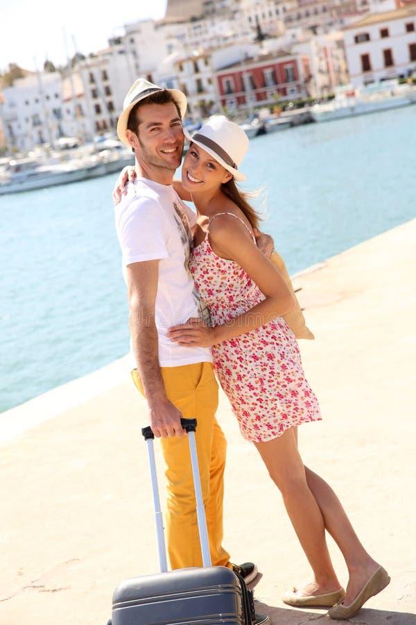 Pares alegres com a mala de viagem em Ibiza foto de stock royalty free