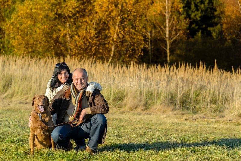 Pares alegres com o cão no campo do outono fotos de stock
