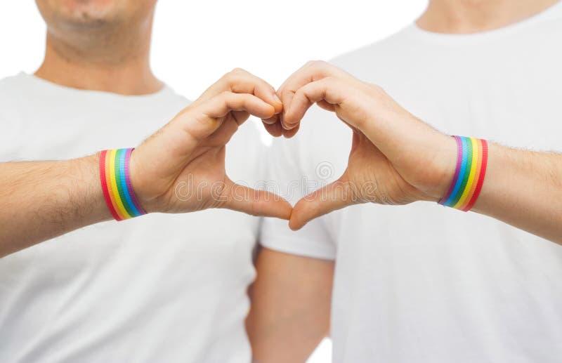 Pares alegres com punhos do arco-íris e coração da mão fotografia de stock