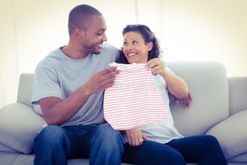 Pares alegres com roupa do bebê imagens de stock