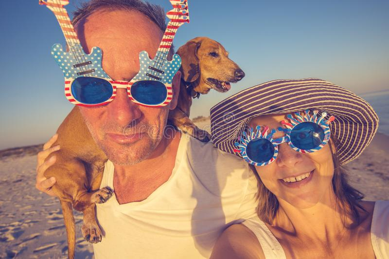 Pares alegres com um cão pequeno que toma o selfie imagens de stock