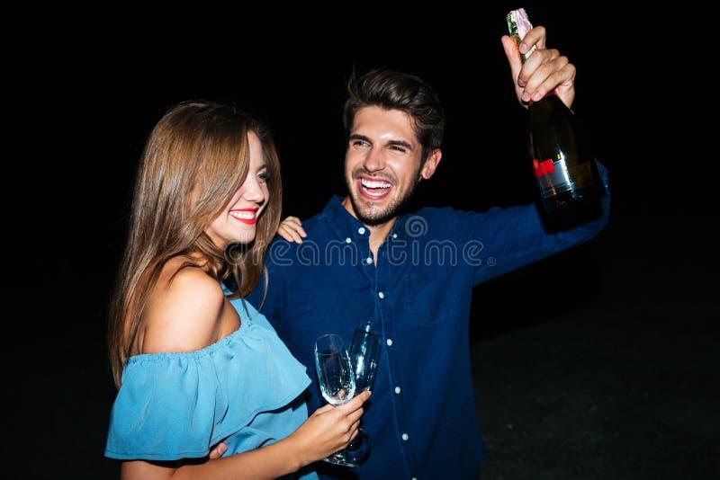 Pares alegres con los vidrios y la botella de champán que se divierte imagenes de archivo