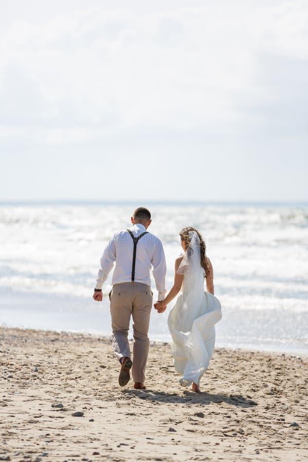 Pares alegres de la boda en la playa fotografía de archivo libre de regalías