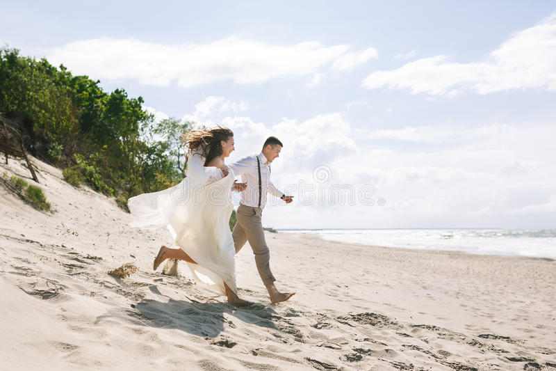 Pares alegres de la boda en la playa foto de archivo