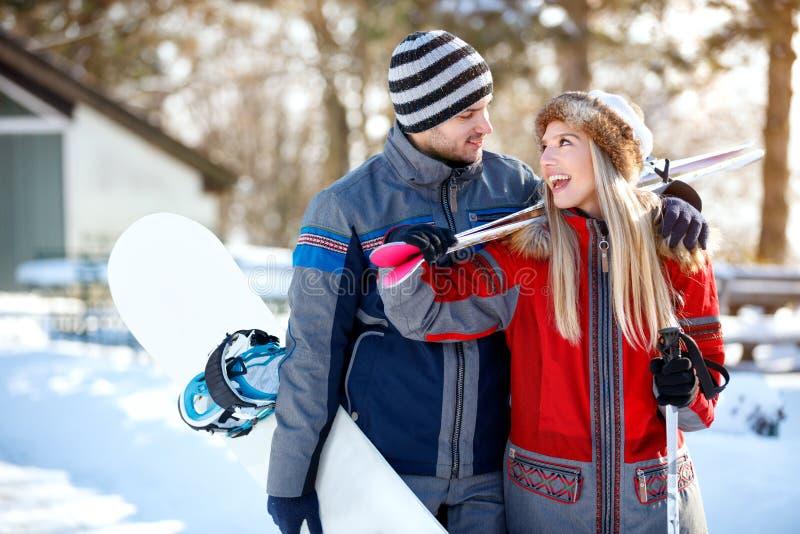 Pares alegres dos esquiadores que vão esquiar terreno fotografia de stock