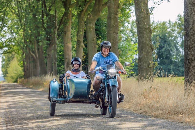 Pares alegres en el motor clásico con el coche lateral en el campo, Países Bajos fotografía de archivo