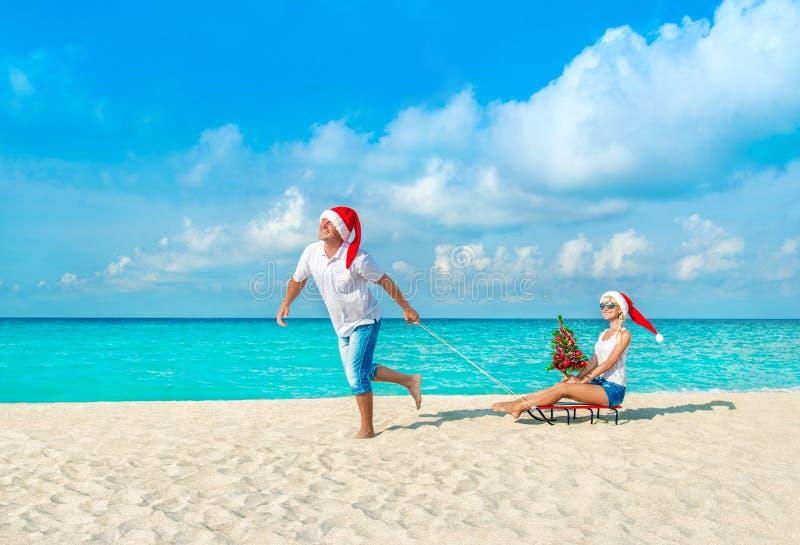 Pares alegres en los sombreros rojos de Papá Noel que caminan en la playa arenosa del océano tropical con los trineos, el abeto a imagen de archivo