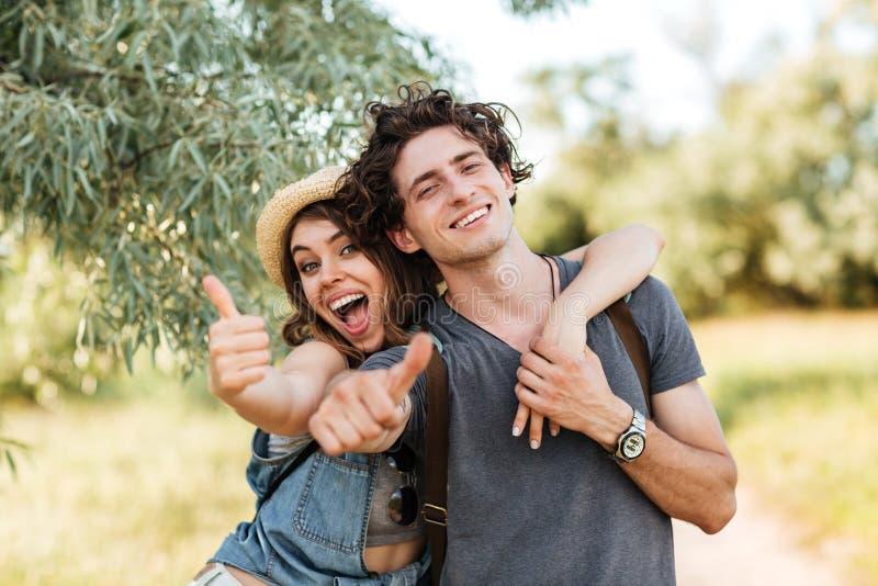 Pares alegres felices jovenes que muestran los pulgares para arriba y el abrazo fotos de archivo