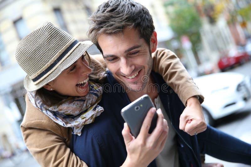 Pares alegres felices que consiguen buenas noticias en smartphone imagen de archivo