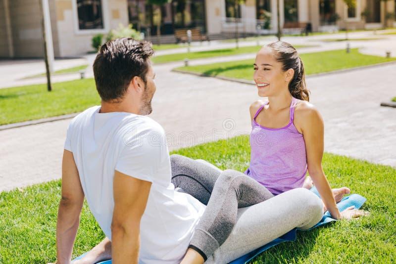 Pares alegres felices que se sientan en la estera de la yoga fotos de archivo libres de regalías