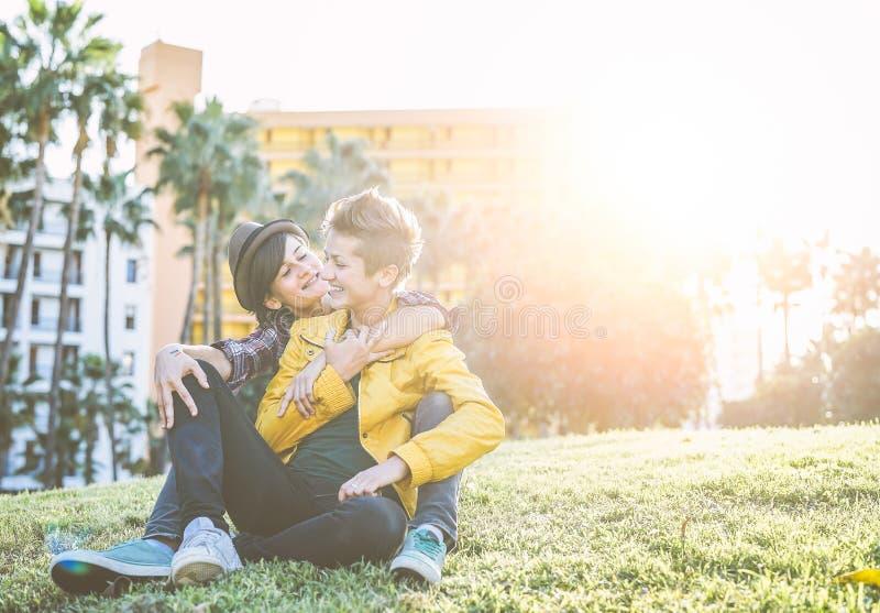 Pares alegres felizes que abraçam e que riem junto o assento na grama em um parque - lésbica das jovens mulheres que têm um momen imagem de stock royalty free