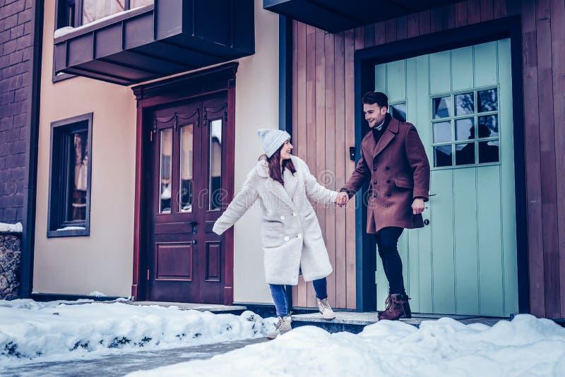 Pares alegres felizes que correm fora da casa para a caminhada no inverno fotos de stock