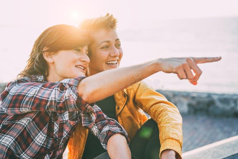 Pares alegres felizes que datam na praia no por do sol - lésbica novas que têm o divertimento que aprecia o tempo junto exterior fotos de stock royalty free