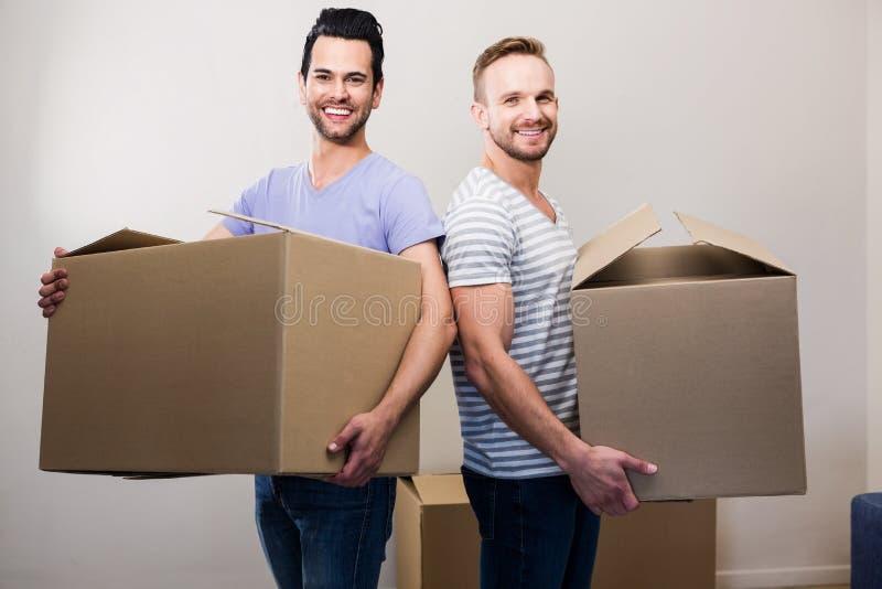 Pares alegres felizes que guardam caixas fotos de stock