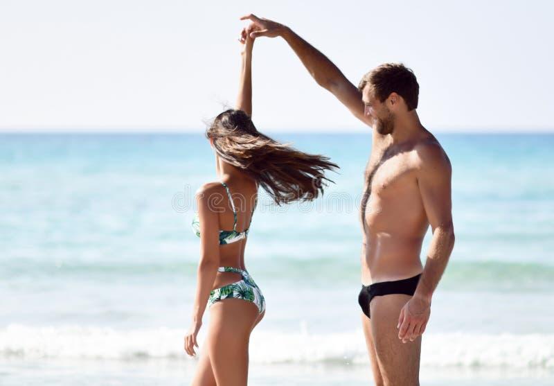 Pares alegres felizes que têm a dança do divertimento que corre no mar junto Férias românticas, amor da lua de mel foto de stock