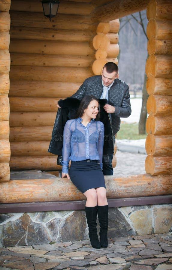Pares alegres jovenes en una cabina en scape romántico en invierno imagen de archivo libre de regalías