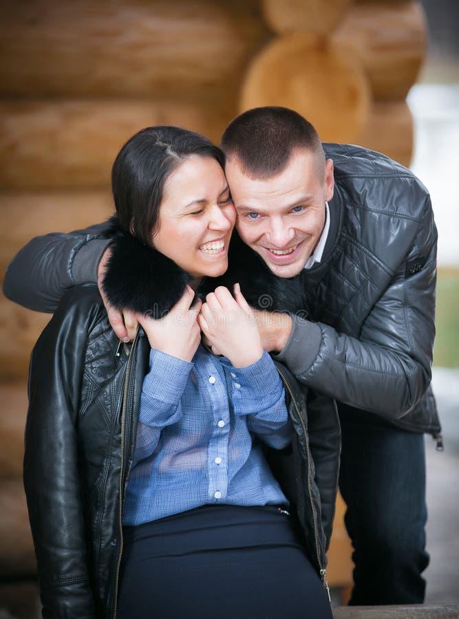Pares alegres jovenes en una cabina en scape romántico en invierno fotos de archivo