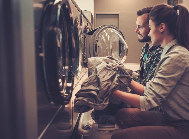 Pares alegres jovenes que hacen el lavadero junto en la tienda de la lavandería foto de archivo libre de regalías