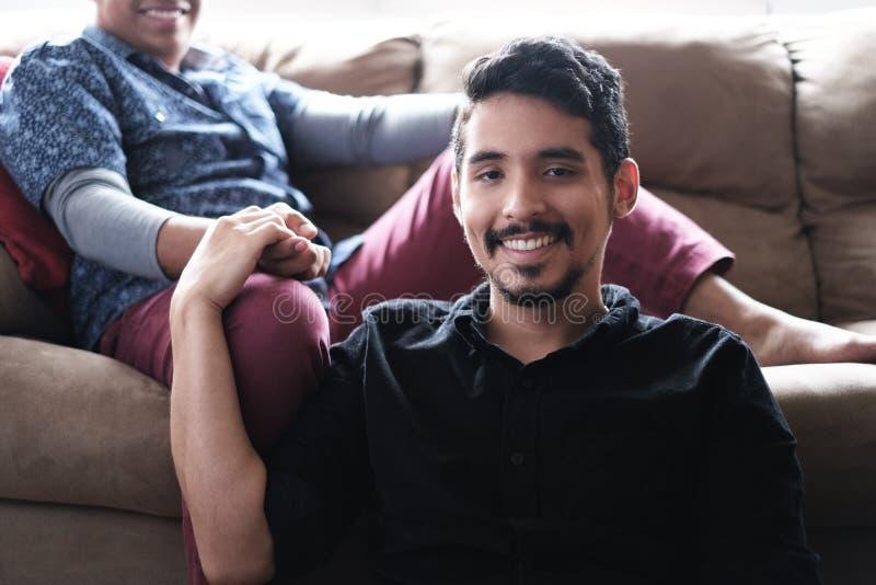 Pares alegres latino-americanos que guardam as mãos no sofá em casa fotografia de stock