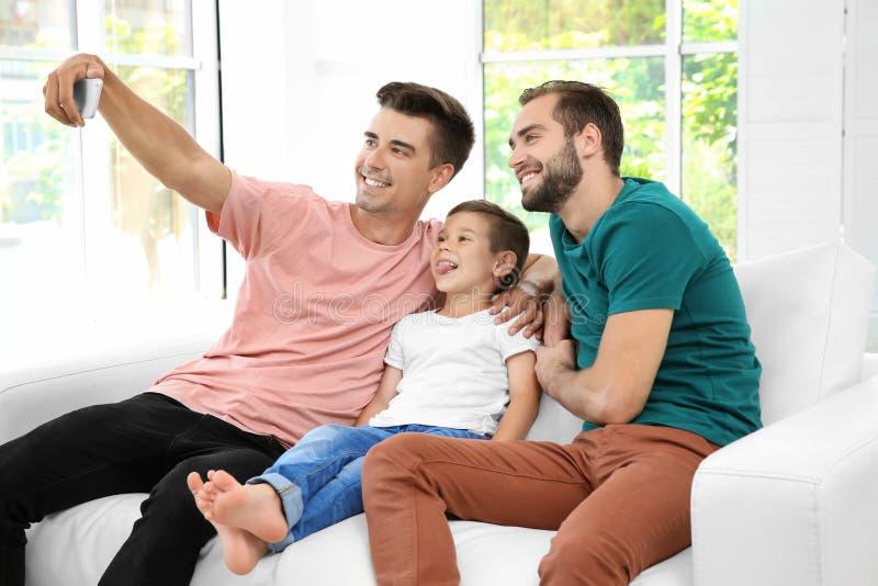 Pares alegres masculinos com o filho adotivo que toma o selfie fotografia de stock