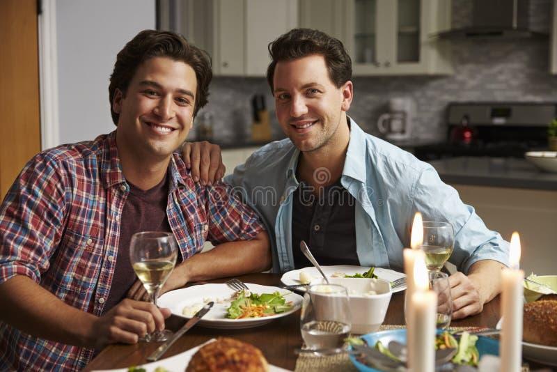 Pares alegres masculinos em casa para um olhar romântico do jantar à câmera imagem de stock royalty free