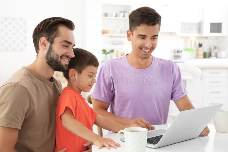 Pares alegres masculinos felizes com filho adotivo em casa foto de stock royalty free