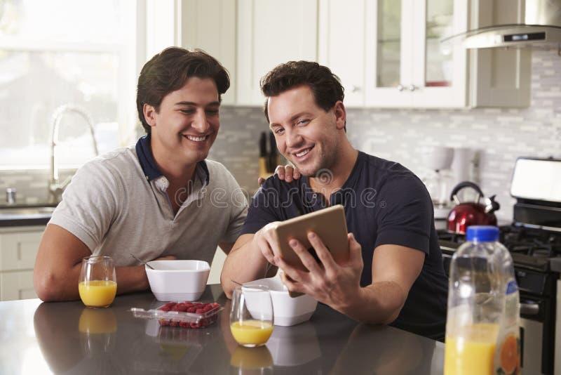 Pares alegres masculinos que olham o tablet pc sobre o café da manhã imagem de stock royalty free